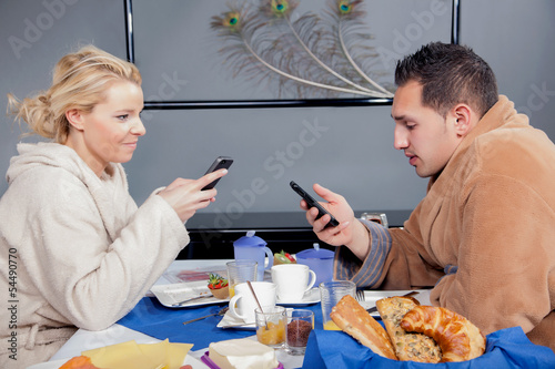 Young couple in bathrobes eating breakfast