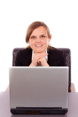 Young businesswoman sitting at office desk with laptop and looki