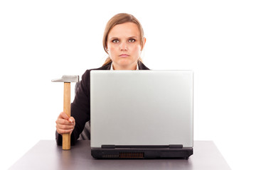 Serious businesswoman with a hammer sitting at office desk