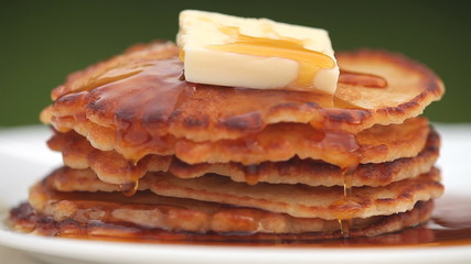 stack of pancakes with pouring maple syrup