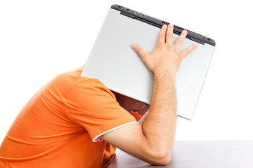 Exhausted young man covering his head with his laptop