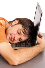 Young man taking a nap on his laptop