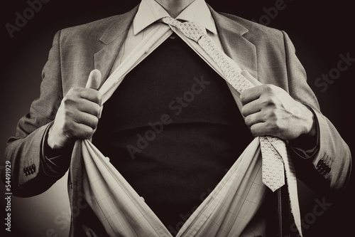 Conceptual image of a man tearing off his shirt