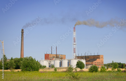 Working electric power plant over blue sky.