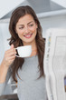 Woman reading a newspaper while holding a cup of coffee