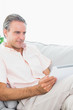 Smiling man relaxing on his couch using tablet pc