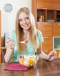 blonde girl eating  fruit salad  in home