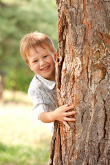 Little boy looking out from behind tree.