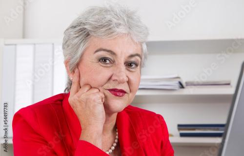 Gesicht einer grauhaarigen älteren Frau mit Falten im Büro