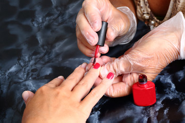 Master covers the red gel nails in the salon