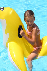 Happy girl swimming at childrens inflatable toy