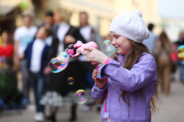 girl is playing with soap bubbles gun on holiday of spring