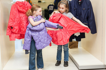 Two cute girls try on clothes in modern store