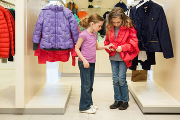 Two modern girls try on clothes in a store
