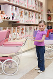 Girl in toy storewith rows of dolls purchased buggy