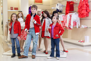 Boy with little girls trying on clothes together with mannequins