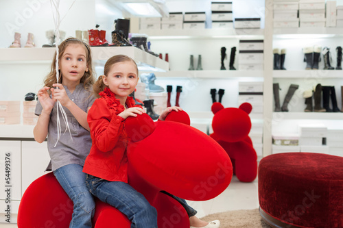 Two girls having fun in toy at store childrens shoes