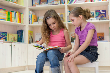 Two girls are concentrated in library reading a book