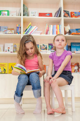 Two little girls are reading an interesting book