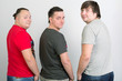 Three gay men in T-shirts wrapped from behind