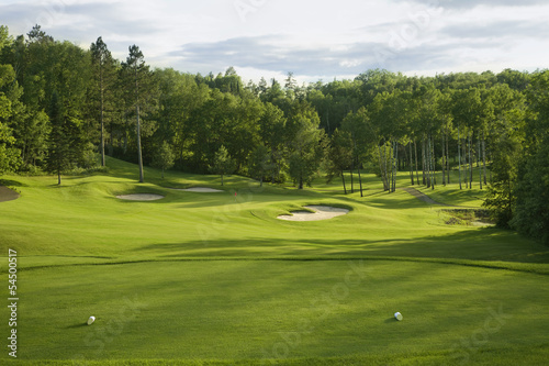 canvas print picture Golf green with bunkers in afternoon sunlight