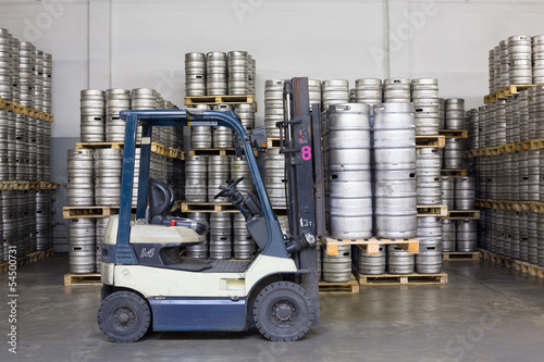 Forklift with beer kegs in stock brewery