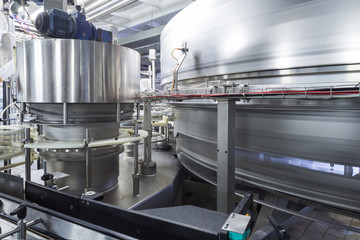 Large shiny tanks and tubing in brewery