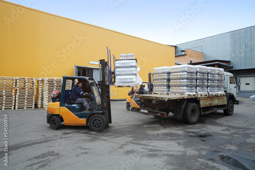 Forklift loading pallets of beer bottles on the truck