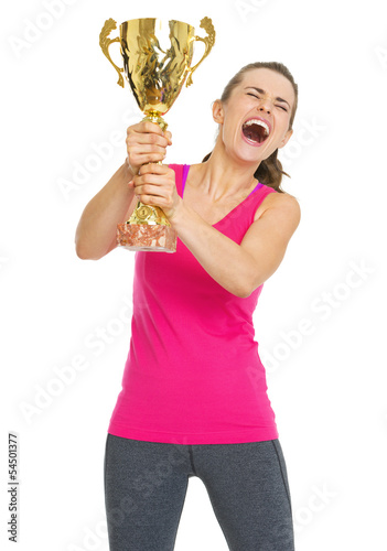 Happy fitness young woman holding gold trophy cup