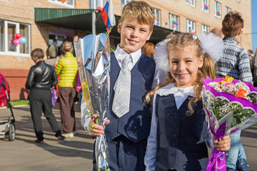 Sister and brother with flowers on first day of school