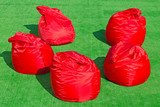 Five soft red chairs in the form of bags on the field