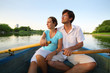 Young couple floating down river on boat with oars