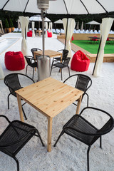 The cozy interior of the open air cafe with red poufs