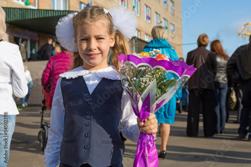 Little girl with the flowers on the first day of school
