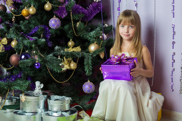 The smiling little girl with a gift sitting under Christmas tree