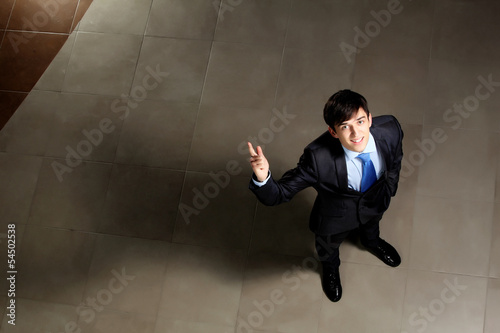 Young businessman pointing with finger