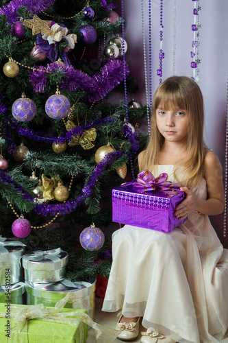 The beautiful girl with a gift sitting under Christmas tree