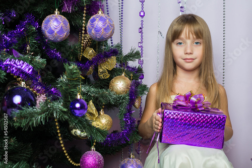 The beautiful little girl with gift sitting under Christmas tree