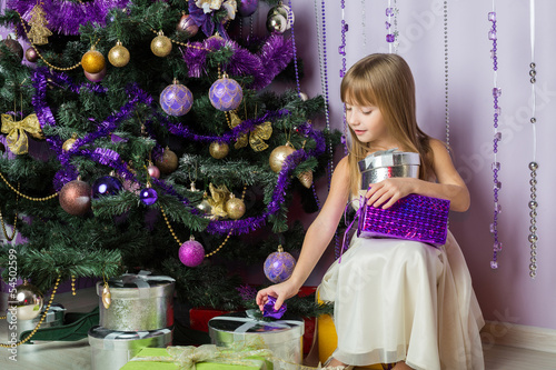 The little girl with a gifts sitting under Christmas tree