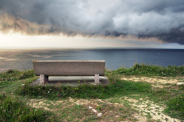 seat near sea with storm coming