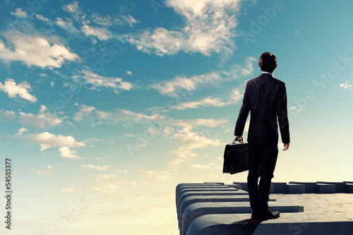 Businessman on top of building