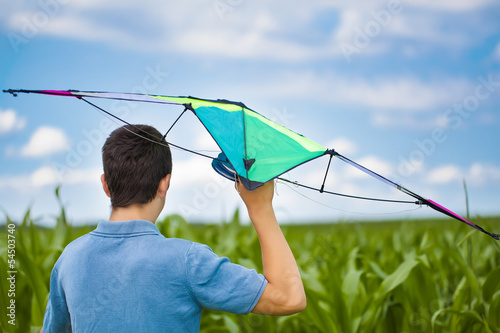 Teen with kite on a corn field in summer