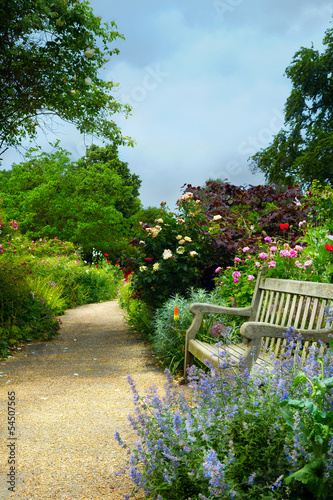 Leinwandbild Motiv Art bench and flowers in the morning in an English park