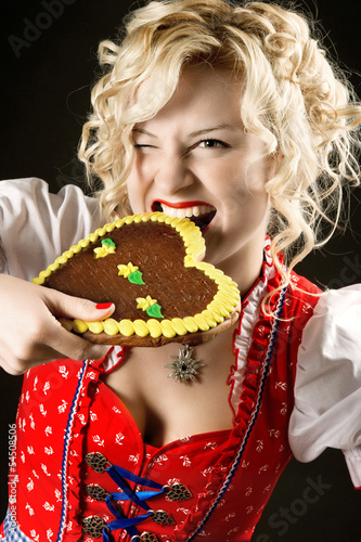 portrait of funny girl in dirndl with typical oktoberfest cookie