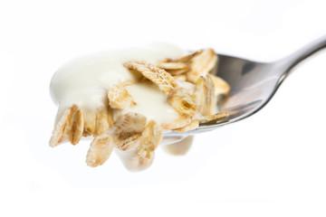 Löffel mit Joghurt und Haferflocken isoliert auf weißem Hinter