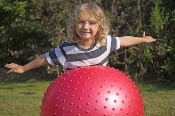 Blond boy is playing with gymnastic ball