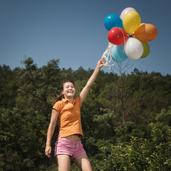 Beautiful and athletic Girl jumping with balloons on a green