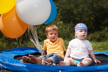 children on a trampoline with balloons