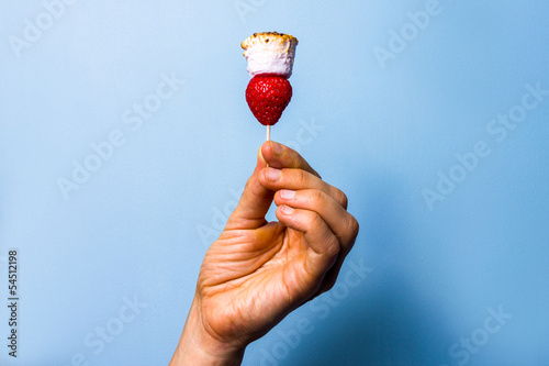 Woman's hand holding a toasted marshmallow and strawberry