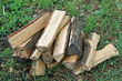 Stack of chopped firewood on natural green background close-up